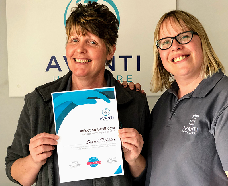 Lucy gives Sarah here induction certificate at Avanti Homecare office.